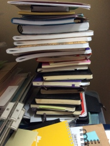 precarious pile of some (not all) used and new notebooks in my home office